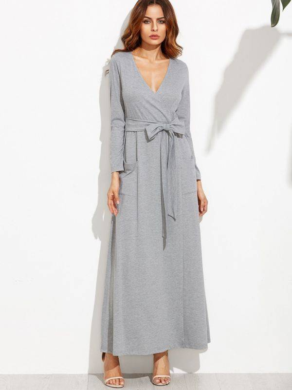 A long gray dress with a tie on the middle and a long sleeve
