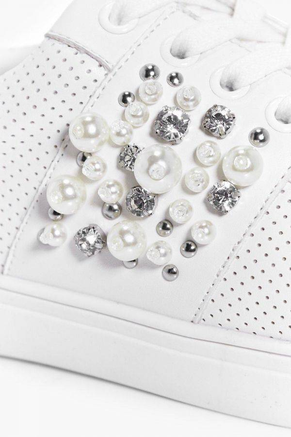 An athletic shoe studded with diamonds and pearls