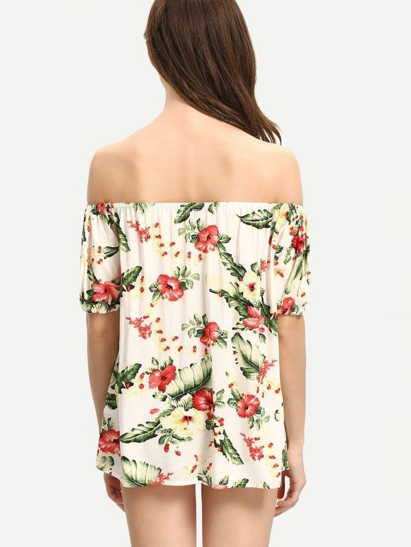 A white blouse with flower print and an open shoulder